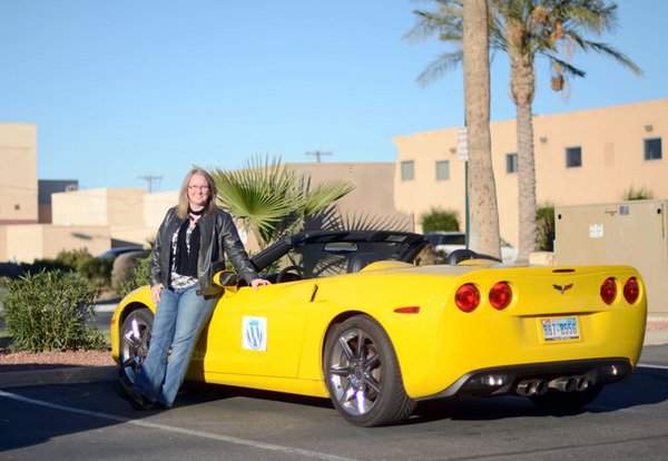 Lisa Sabin-Wilson posing with yellow WordPress Corvette