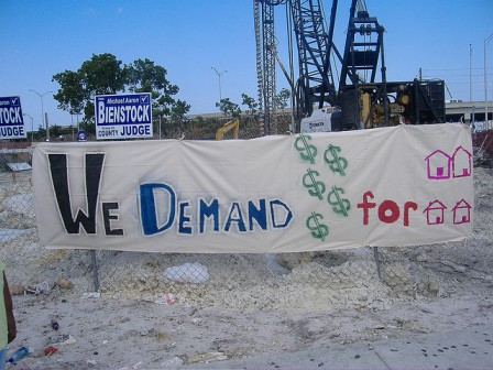 """We demand money for houses"" protest sign"