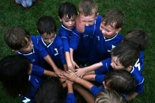 Photo of kids soccer team doign an end of practice cheer