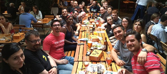 Group photo with many members of the WPMU DEV team after eating dinner together, sitting at a long table.