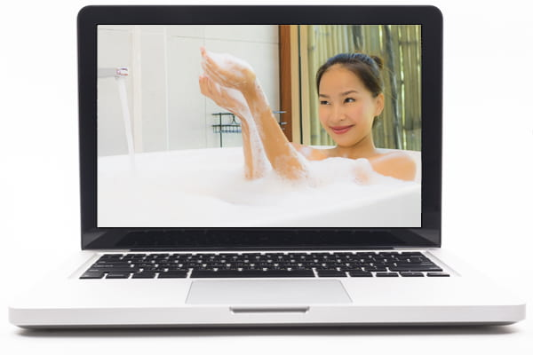 Laptop screen showing image of woman taking a bubble bath.