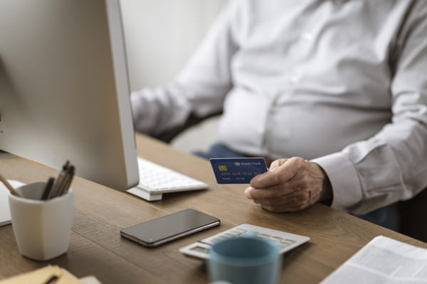 Image of man with credit card making an online purchase.